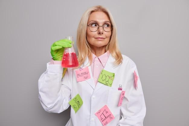 Chemiker trägt runde brille weißen mantel mit geklebten aufklebern geschriebene formeln hält glaskolben mit roter flüssigkeit nach dem mischen von reagenzien isoliert auf grau