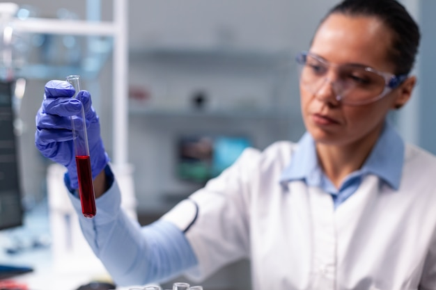 Chemikerdoktor, der das blutreagenzröhrchen analysiert, das am chemievirusexperiment arbeitet
