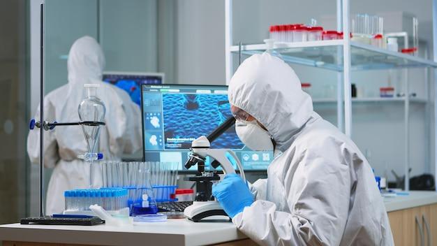 Chemikerforscher bei der gesamtbetrachtung von bakterienproben aus glasgeräten in einem modern ausgestatteten labor. untersuchung der impfstoffevolution mit hightech zur erforschung der behandlung gegen das covid19-virus
