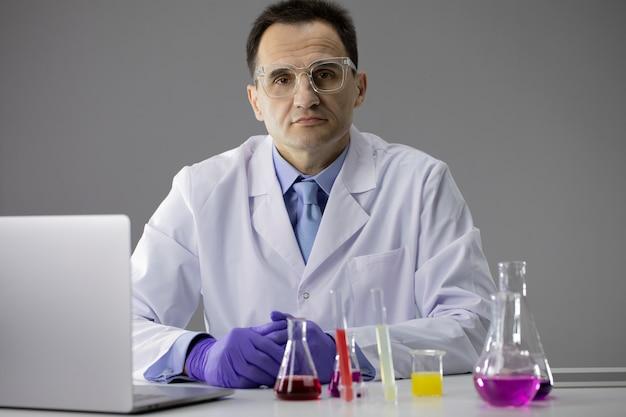Chemikerforscher, die flaschen arbeiteten, füllten bunte chemische lösungen und laptop