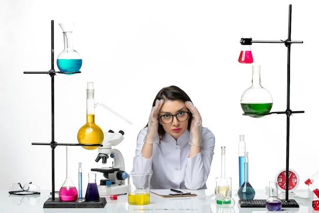 Chemikerin der vorderansicht im medizinischen anzug, der um tisch mit lösungen auf hellweißem hintergrundlaborvirus-covid-pandemie-wissenschaft sitzt