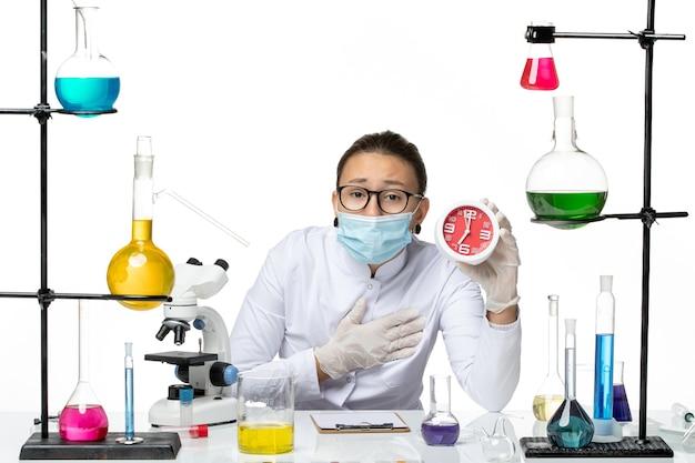Chemikerin der vorderansicht im medizinischen anzug mit der maske, die rote uhren auf dem covid-splash-labor der weißen hintergrundviruschemie hält