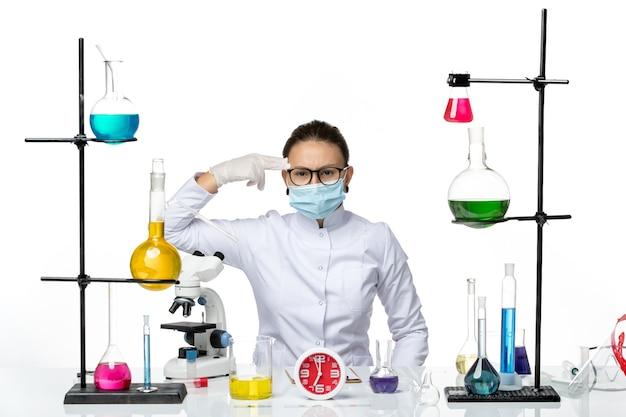 Chemikerin der vorderansicht im medizinischen anzug mit maske, die mit lösungen auf covid-splash des weißen schreibtischchemie-viruslabors sitzt