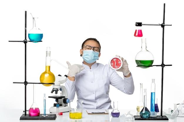 Chemikerin der vorderansicht im medizinischen anzug mit maske, die rote uhren auf einem weißen hintergrund-spritzvirus-chemie-covidlabor hält