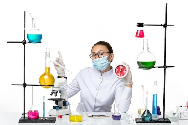 Chemikerin der vorderansicht im medizinischen anzug mit maske, die rote uhren auf hellweißem hintergrundviruslabor-chemie-covid-splash hält