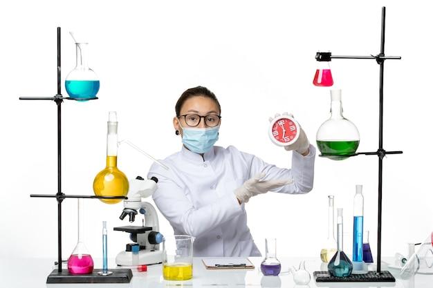 Chemikerin der vorderansicht im medizinischen anzug mit maske, die uhren auf dem hellweißen hintergrundviruslaborchemie-covid-spritzer hält