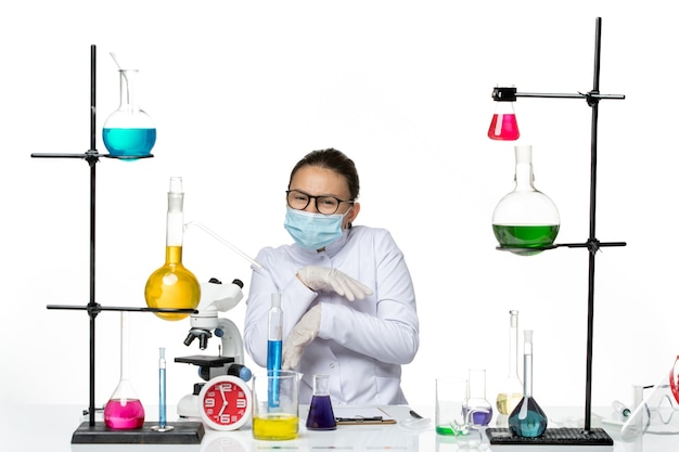 Chemikerin der vorderansicht im medizinischen anzug mit maske, die vor tisch mit lösungen auf dem hellweißen hintergrundvirus-chemielabor-covid-spritzer sitzt