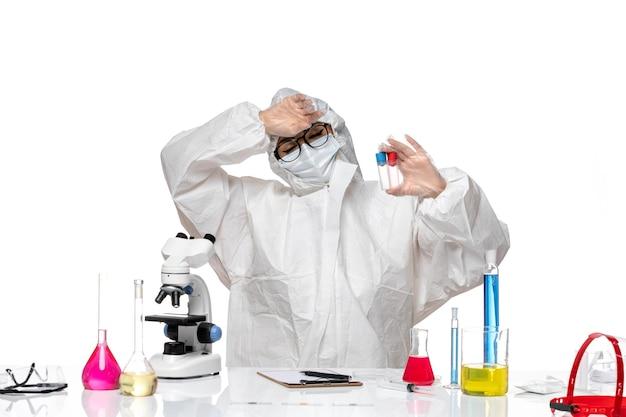Chemikerin der vorderansicht im speziellen schutzanzug, der leere flaschen auf weißem hintergrundgesundheitsvirus-chemie-covid hält