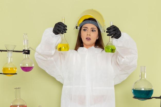 Chemikerin der vorderansicht im speziellen schutzanzug, der mit lösungen auf grünem schreibtisch arbeitet