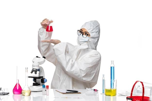 Chemikerin der vorderansicht im speziellen schutzanzug, der rote lösung auf covid-chemie-viruslabor des weißen hintergrunds hält