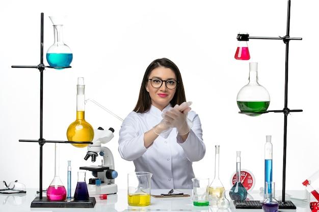 Chemikerin der vorderansicht im weißen medizinischen anzug, der gerade mit lösungen auf weißem hintergrundwissen-covid-lab-pandemievirus sitzt