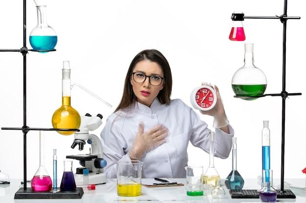 Chemikerin der vorderansicht im weißen medizinischen anzug, der rote uhren auf hellweißem hintergrund-wissenschaftsvirus-covid-pandemielabor hält