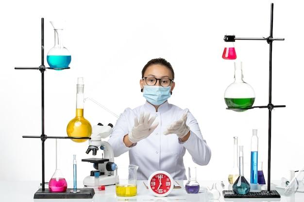 Chemikerin der vorderansicht im weißen medizinischen anzug mit maske, die gerade auf dem covid-splash-labor des weißen hintergrundchemikervirus sitzt