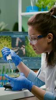 Chemikerin, die dna-flüssigkeit aus dem reagenzglas mit mikropipette nimmt, die in petrischale steckt, die genetische mutation analysiert