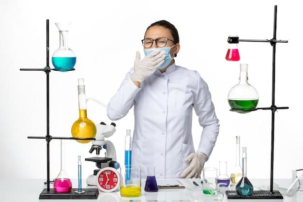 Chemikerin in der vorderansicht im medizinischen anzug mit gähnender maske auf covid-splash des viruslabors des weißen hintergrundvirus