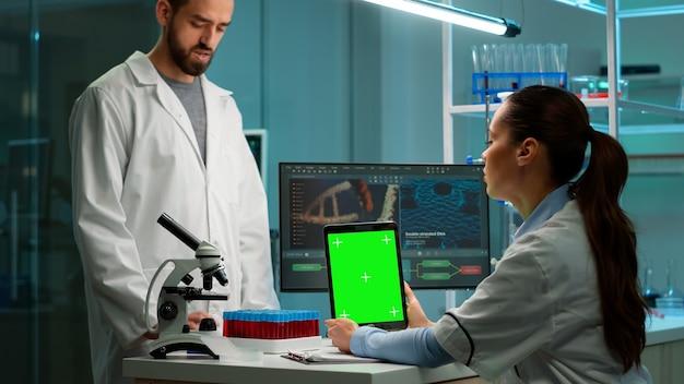 Chemikerin mit grüner mock-up-bildschirmtablette am schreibtisch. im hintergrund technologieforschung, entwicklungslabor mit facharzt im bereich high-tech-design