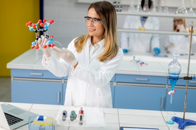 Chemikerin mit schutzbrille hält molekulares modell im labor