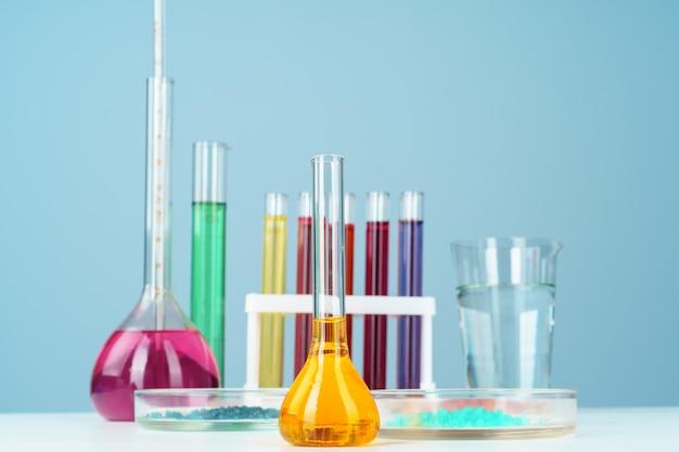 Chemische laborglaswaren mit verschiedenen farbigen flüssigkeiten auf tabelle