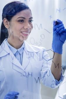 Chemische reaktion. positive glückliche kluge frau, die einen textmarker hält und notizen macht, während sie an einer formel arbeitet
