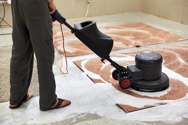 Chemische teppichreinigung mit professioneller scheibenmaschine. vorzeitiger frühjahrsputz oder regelmäßige reinigung