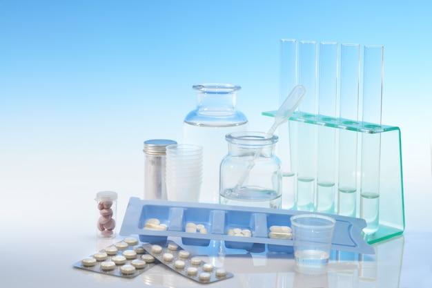 Chemische und analytische glaswaren und verschiedene pillen auf blau