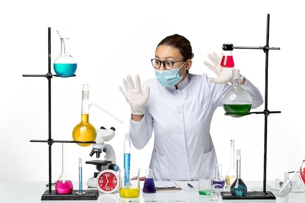 Chemische vorderansicht chemikerin im medizinischen anzug mit maske, die mit lösungen auf covid splash des weißen bodenvirus-chemielabors arbeitet