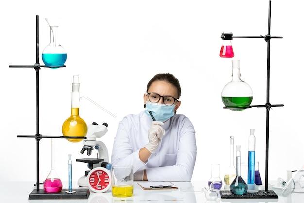 Chemische vorderansicht chemikerin im medizinischen anzug mit maske sitzend mit lösungen, die notizen auf hellweißem hintergrund-spritzlabor-viruschemie-covid schreiben