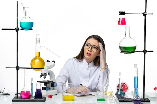 Chemische vorderansicht chemikerin im weißen medizinischen anzug sitzend mit lösungen, die notizen auf weißem hintergrundwissenschaft-pandemievirus-covid-labor schreiben