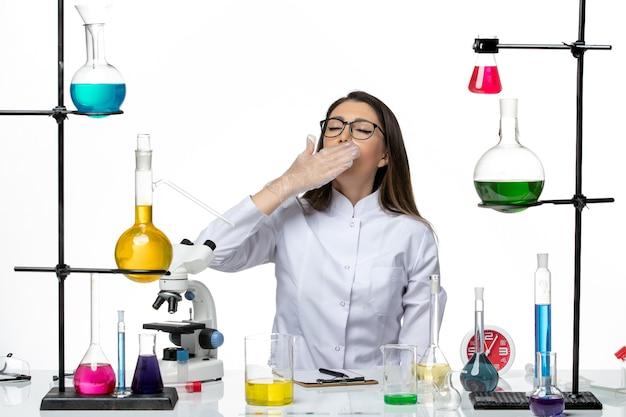 Chemische vorderansicht chemikerin im weißen medizinischen anzug sitzend mit verschiedenen lösungen, die auf weißer hintergrundwissenschaft-viruslabor-covid-pandemie gähnen