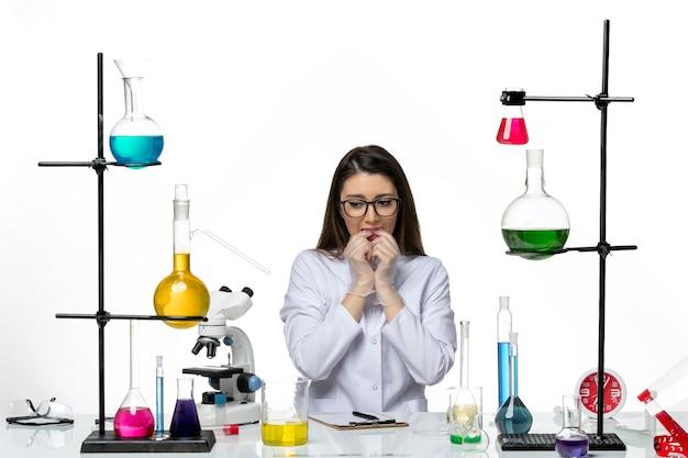 Chemische vorderansicht chemikerin im weißen medizinischen anzug sitzend und nervös auf weißer hintergrundlaborwissenschaft virusvirus-covid-pandemie