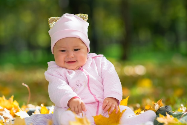 Cherubic kleines baby, das mit bunten blättern in einem herbstpark spielt, während sie auf einem teppich auf dem gras in einer niedrigen winkelansicht sitzt