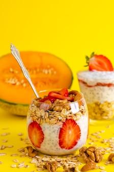 Chia-joghurtpudding mit erdbeeren, haferflocken und nüssen in einem glas auf gelb