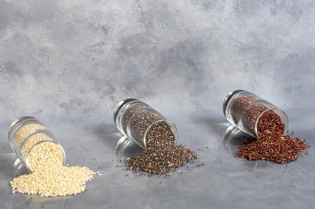 Chia-, leinsamen- und sesamkörner in einer glasschale enthalten gesunde vitamine und mineralien. unter beton.