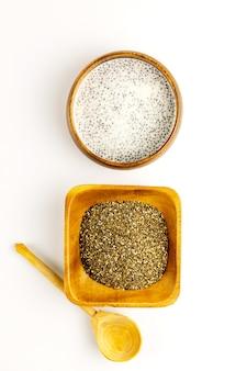 Chia-milchpudding und trockene samen in bambusschalen mit rustikalem holzlöffel. draufsicht. flach liegen. nahansicht. selektiver weichzeichner. textkopierplatz.