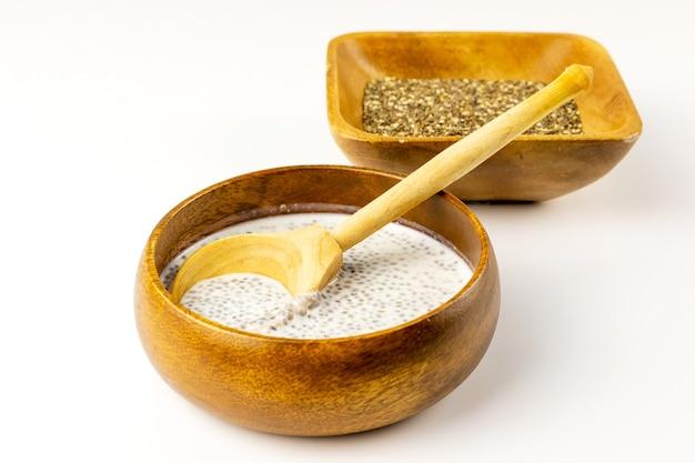 Chia-milchpudding und trockene samen in bambusschalen mit rustikalem holzlöffel. nahansicht. selektiver weichzeichner. textkopierplatz.