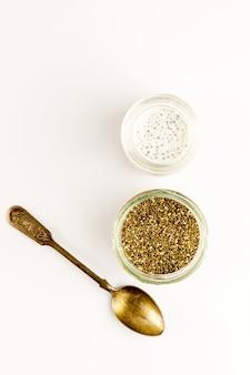 Chia-milchpudding und trockene samen in kleinen glasschalen mit vintage-löffel. draufsicht. flach liegen. nahansicht. selektiver weichzeichner. textkopierplatz.