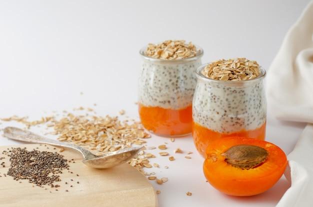 Chia pudding des joghurts mit frischen aprikosen- und haferflocken auf weiß