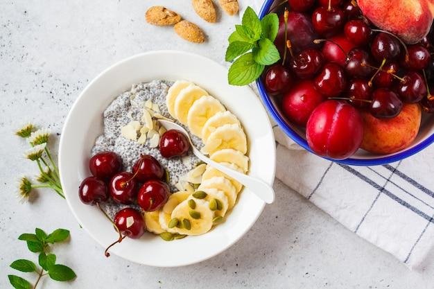 Chia-pudding mit banane, kirsche und nüssen in der weißen platte.