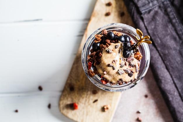 Chia-pudding mit beeren, granola und erdnussbutter im glas, draufsicht