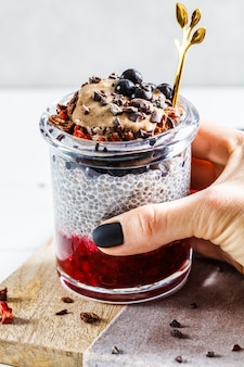 Chia-pudding mit beeren, müsli und erdnussbutter im glas