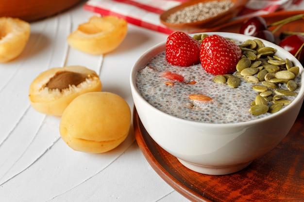 Chia-pudding mit erdbeer- und kürbiskernen auf holztisch