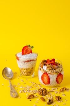 Chia pudding mit erdbeeren, haferflocken und nüssen in einem glas auf gelb