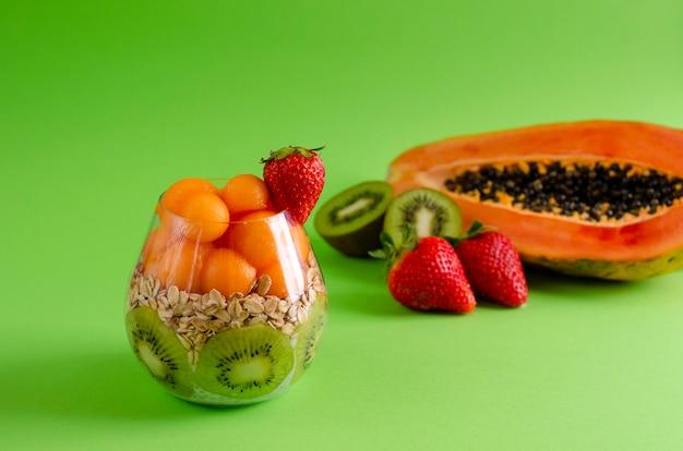 Chia-pudding mit frischen rohen tropischen früchten, hafer blättert für die gesunde ernährung auf grün ab