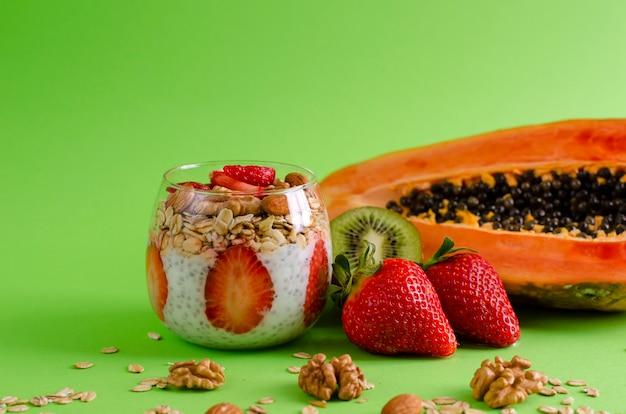 Chia-pudding mit frischen rohen tropischen früchten mit haferflocken und nüssen für die gesunde ernährung auf grün