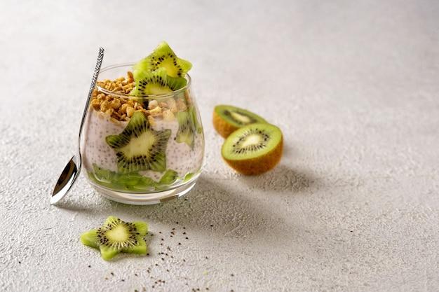 Chia pudding mit kiwi auf grauem hintergrund. gesunde ernährung, superfood. nahaufnahme.