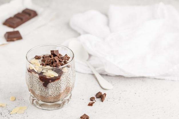 Chia-pudding mit schokolade, mandeln und beerenmarmelade, kopienraum. rohes veganes dessert.