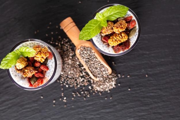 Chia-samen des gesunden lebensmittelkonzeptes, milchpudding mit goji, weiße maulbeere und mischung trockneten samen im kleinen glas auf schwarzem schieferbretthintergrund