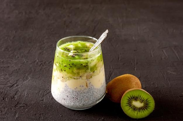Chia-samen-pudding mit kiwi, banane und mango. gesundes detox-frühstück in gläsern auf schwarzem beton