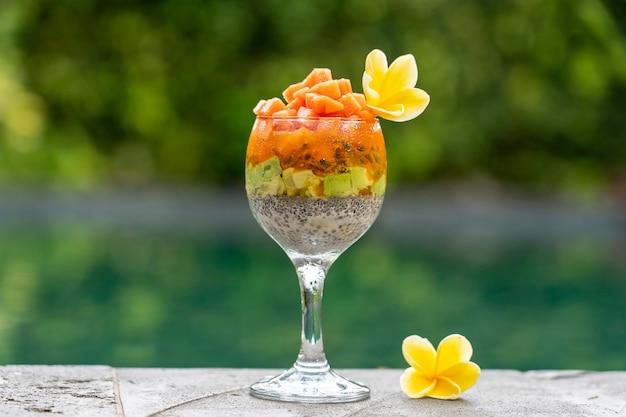 Chia-samen-pudding mit papaya, passionsfrucht, mango und avocado in einem glas zum frühstück auf dem hintergrund des schwimmbadwassers, nahaufnahme. das konzept der gesunden ernährung, superfood