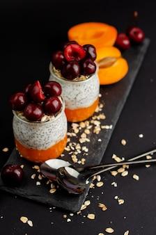 Chia-samenjoghurtpudding mit süßem chrries, zertrümmerter frischer aprikose und hafer auf schwarzem